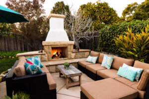 Outdoor fireplace and seating area by Cornerstone Landscapes